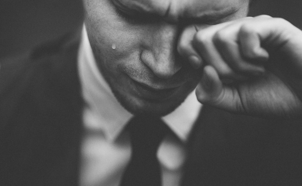 man crying in black and white photo