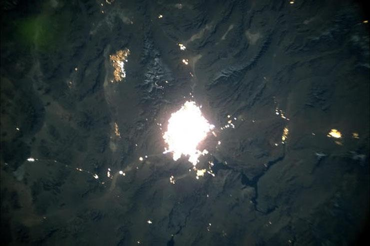 photo from space showing las vegas glowing surrounded by darkness