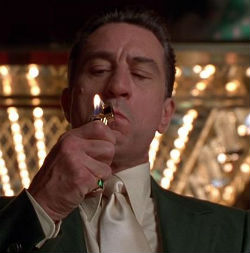 Robert De Niro in movie casino smoking cigarette in front of bright lights