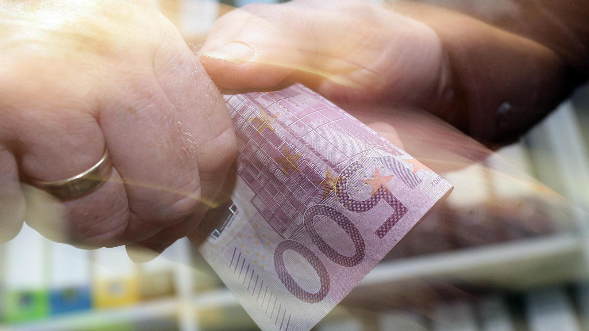 500 Euro Note wird an jemand übergeben.