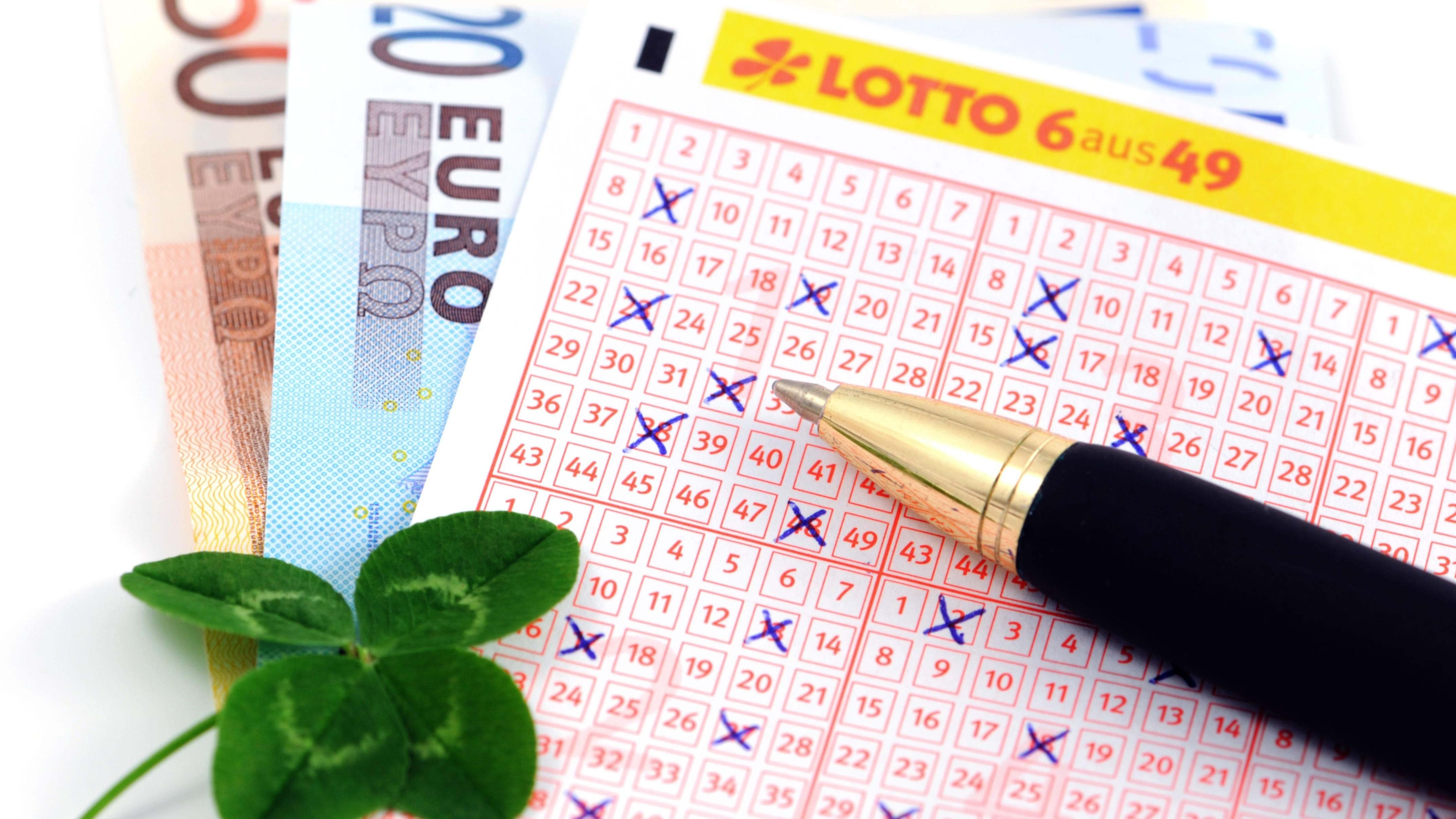 Lottoschein mit Glückskleeblatt und Euroscheinen
