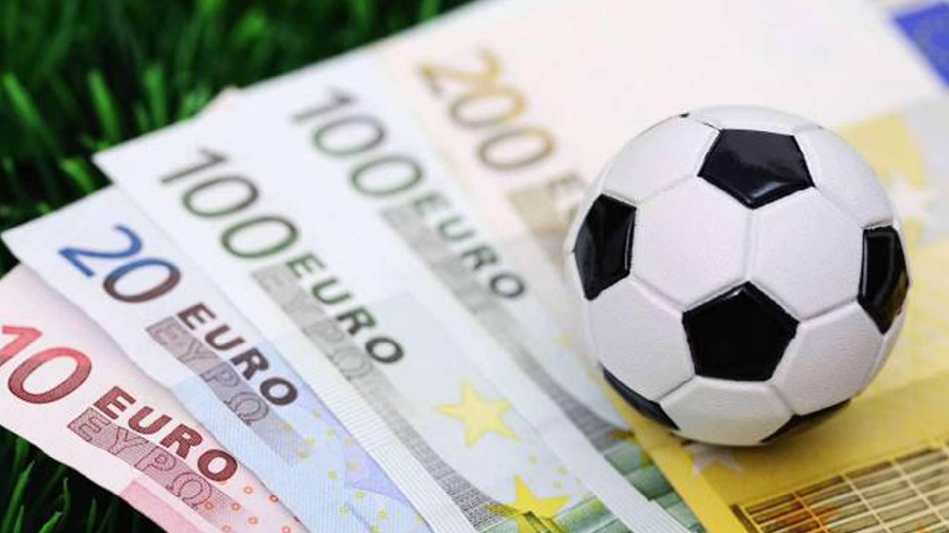 Ein Fußball liegt auf Euroscheinen als Sinnbild für Sportwetten