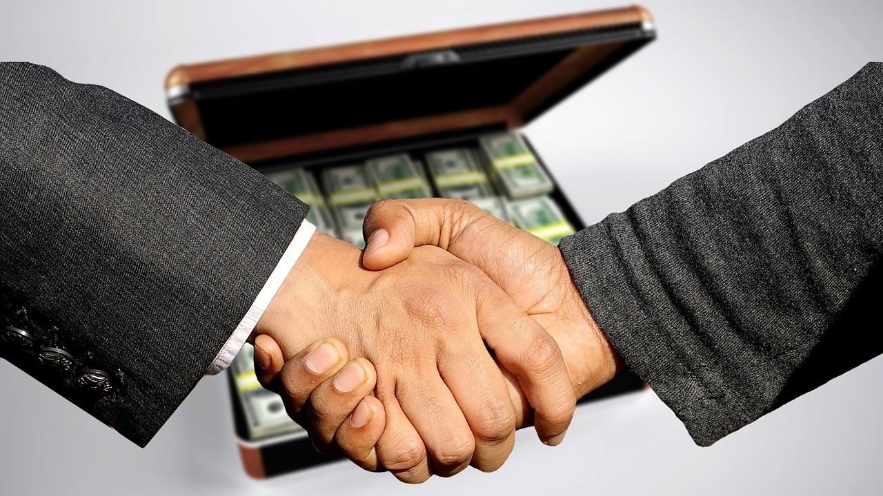 Händeschütteln vor Geldkoffer