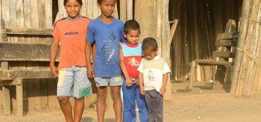 Vier Kinder vor einer Hütte in Südamerika