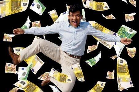 Glücklicher Mann springt im Geldregen