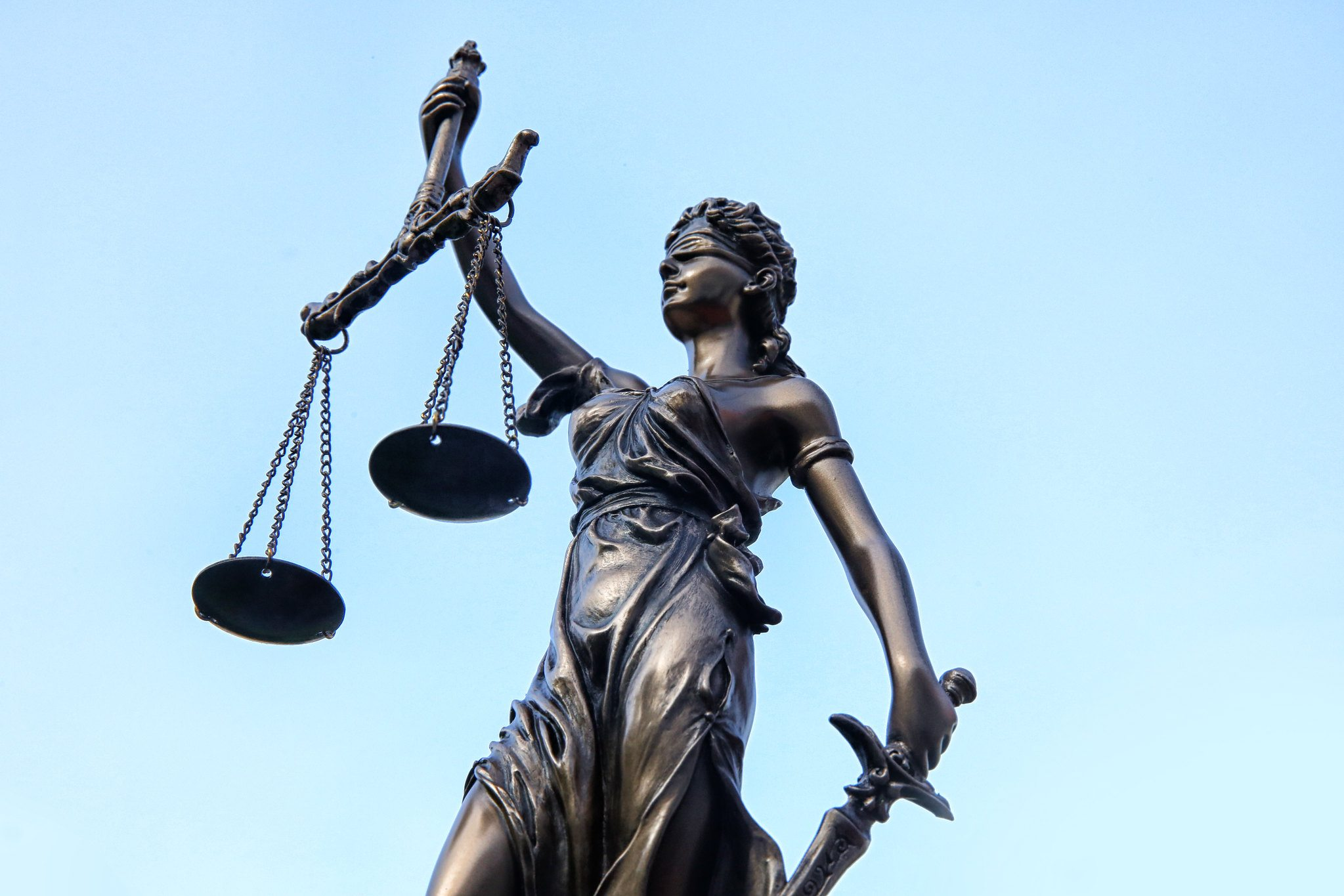 Justitia Statue vor blauem Himmel