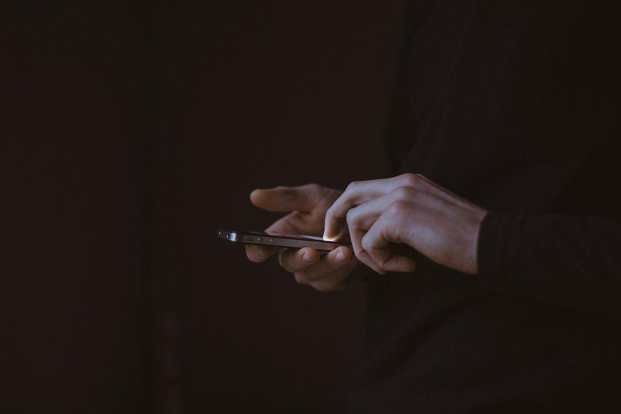 Mann mit Smartphone, SMS schreiben