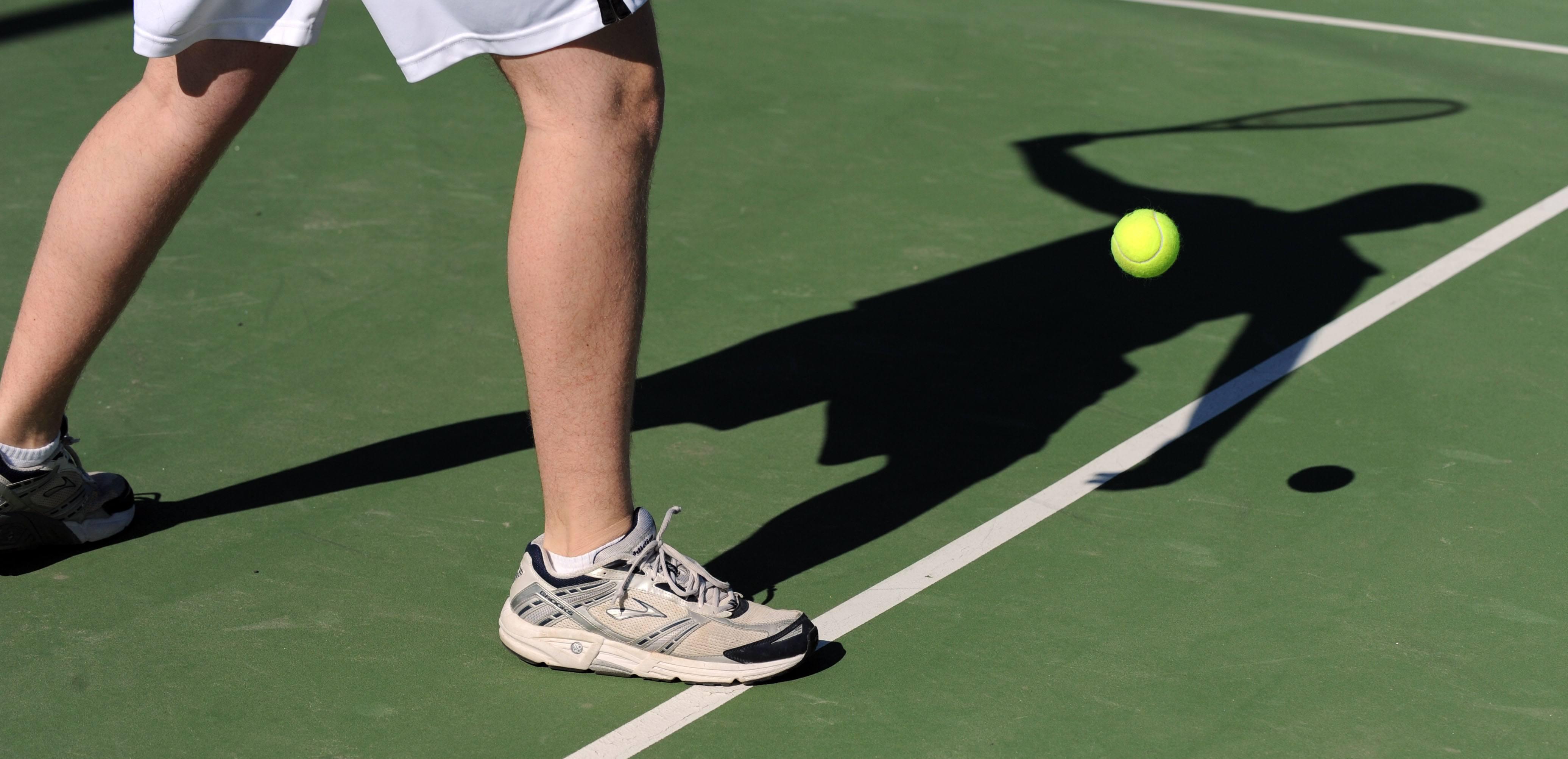 Tennispielerbeine auf dem Platz