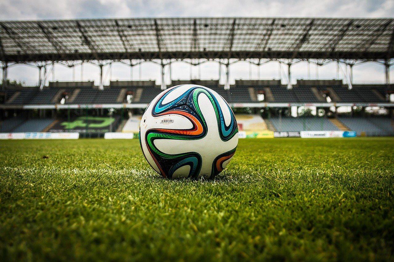 Fussball auf Rasen vor leeren Rängen