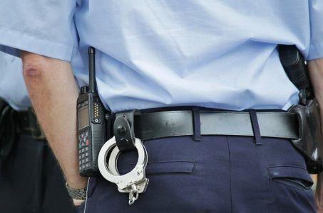 Polizist in Uniform mit Handschellen, Funkgerät und Pistole