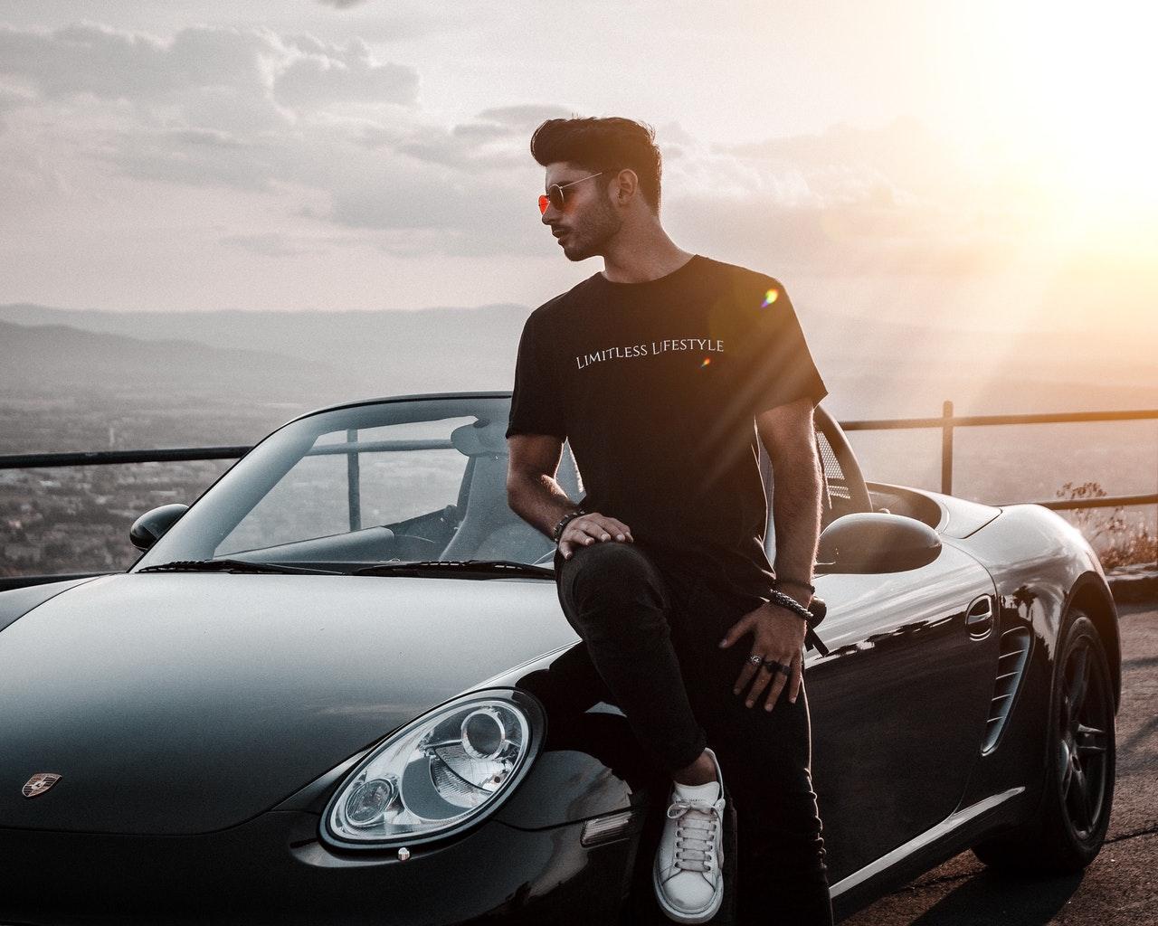 Instagram Influencer mit Auto vor Sonnenuntergang