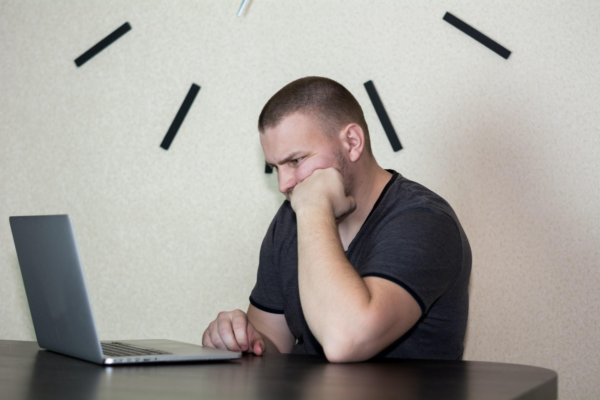 Mann schaut unzufrieden auf Laptop