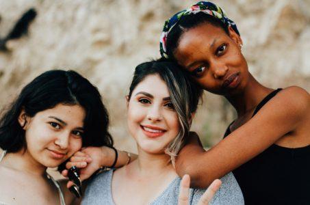 Drei junge Frauen schauen in die Kamera