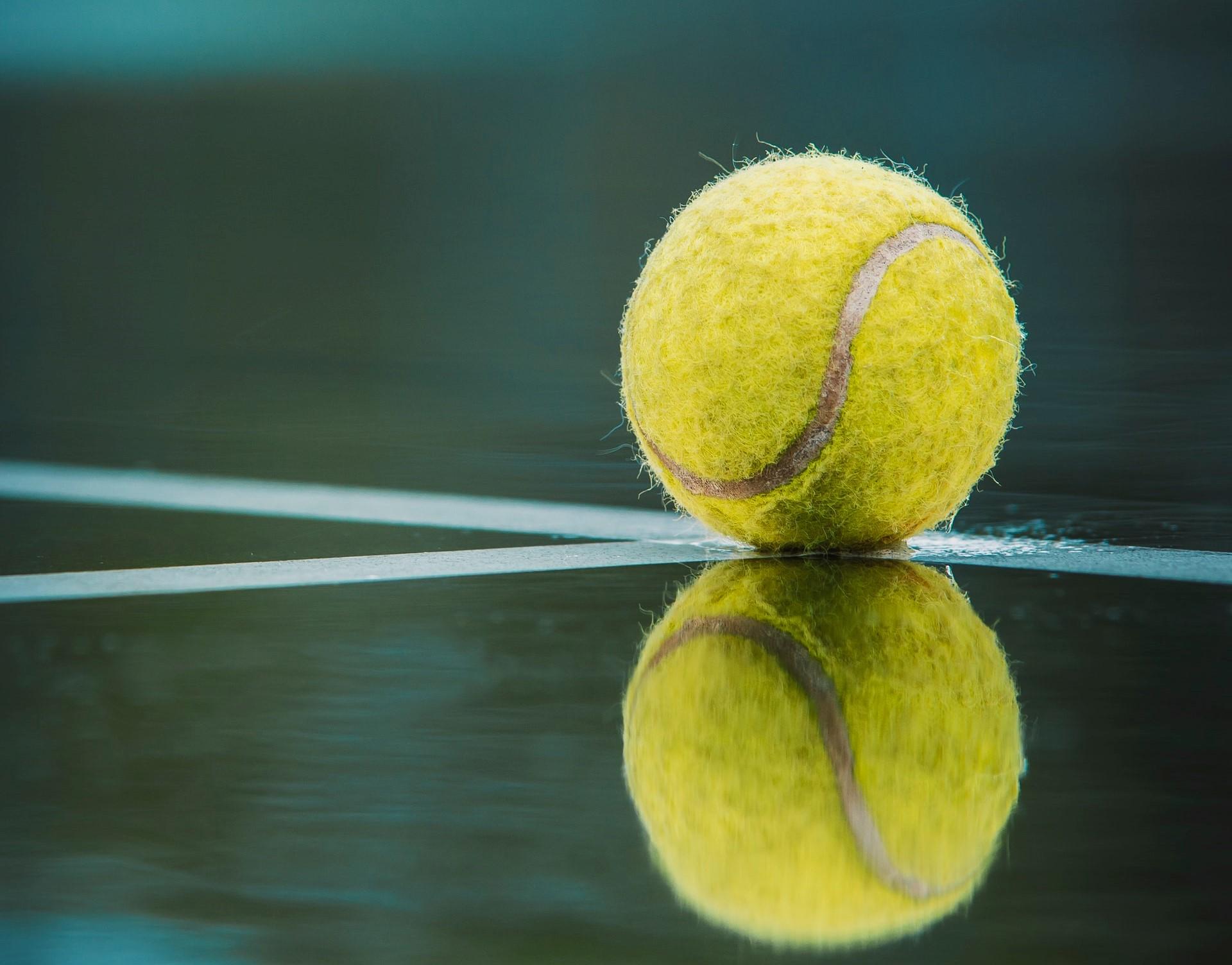 Tennisball spiegelt sich auf Platz