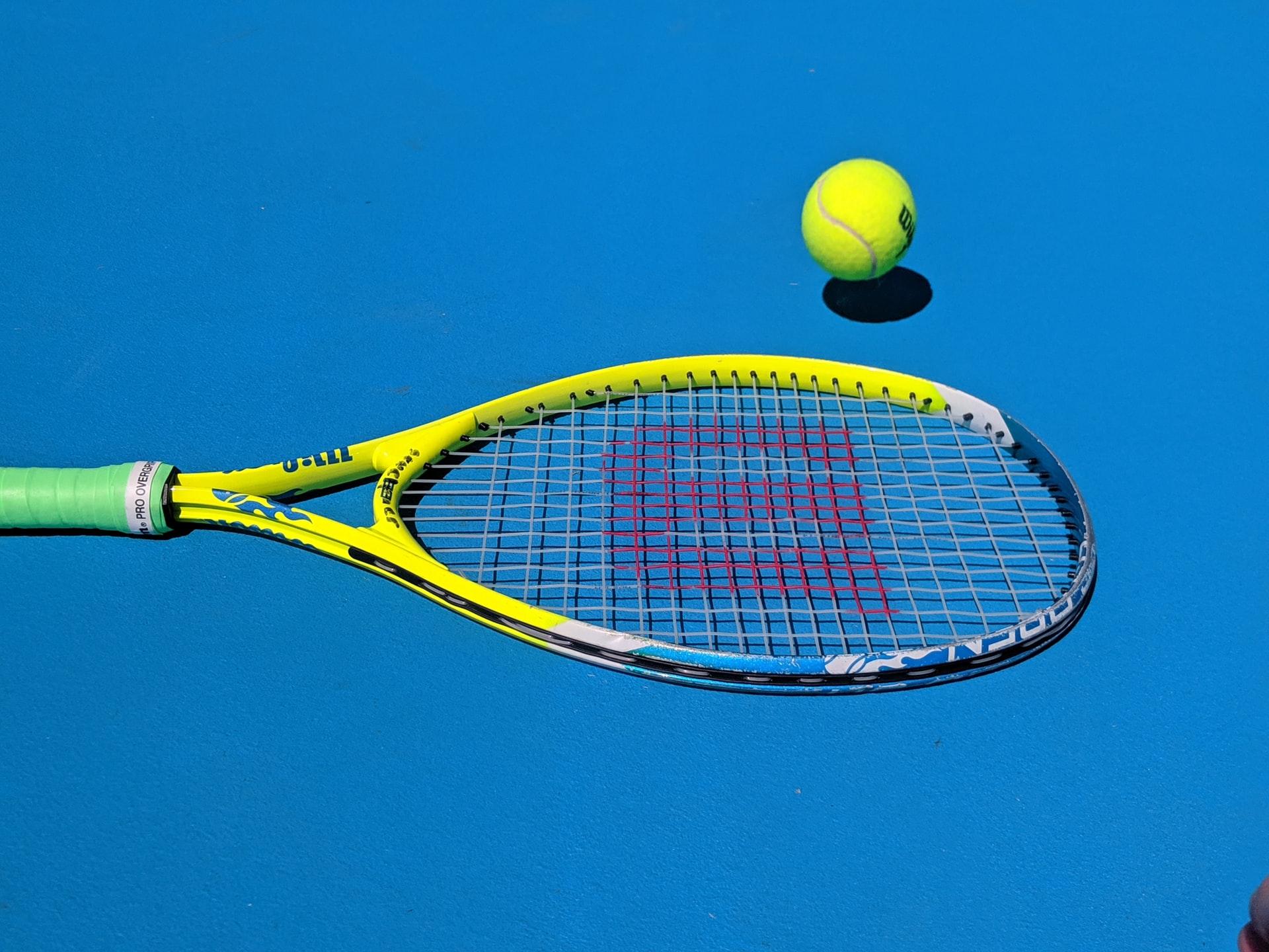 Tennisschlaeger und Ball auf blauem Platz