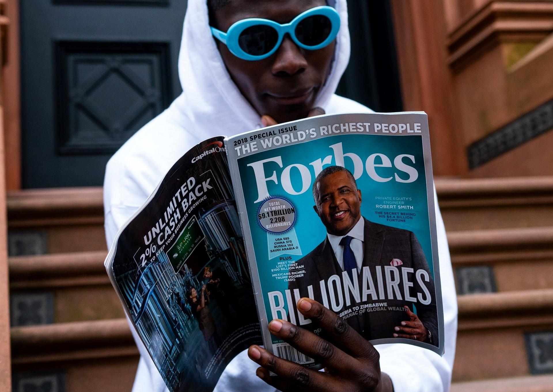 Mann liest im Forbes-Magazin
